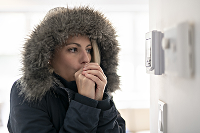 Heating repair in Manasquan, Woman who is cold wearing a winter coat with a furry hood standing in front of thermostat